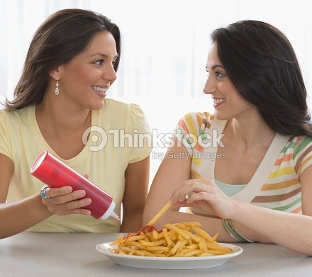 Two Young Women Eating French Fries Stock Photo