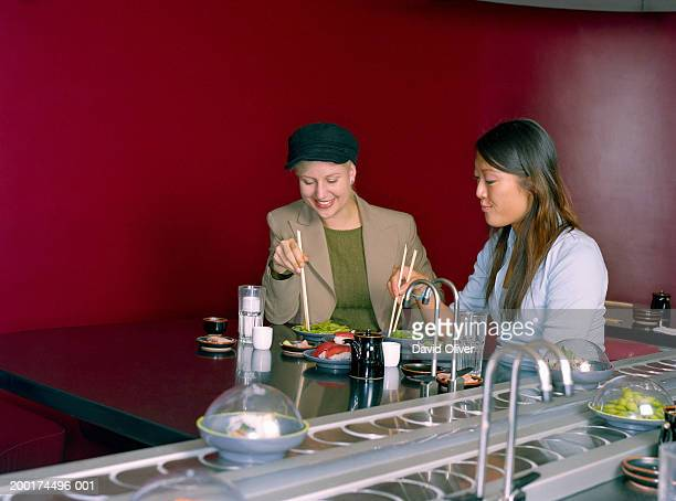 Two young women eating in sushi restaurant