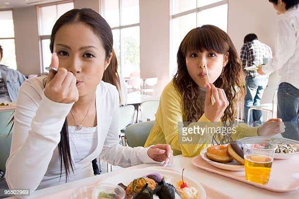 Two Young Women Eating Lunch in Cafeteria