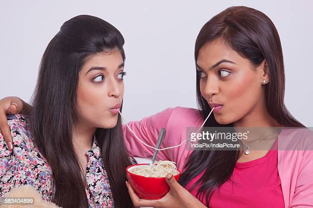 Two young women eating noodles