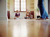 Two young women eating on floor of empty house, laughing