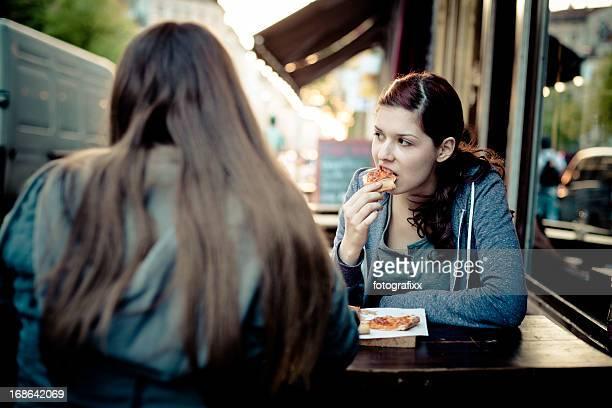 """Zwei junge Frauen Essen pizza in die Straße """""""