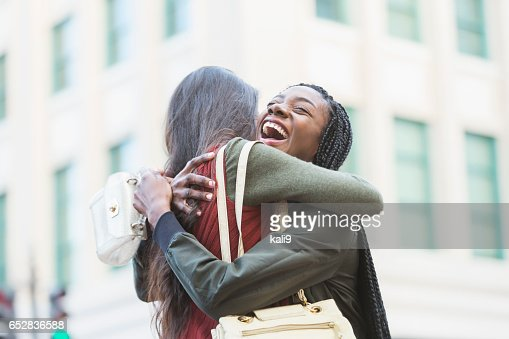 Two young women embracing on street corner : Foto stock