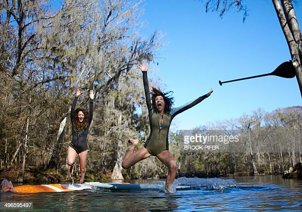 Two young women falling off stand up paddleboard