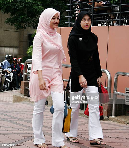 Two young women fashionably dressed in Malaystyle Muslim head scarves and tunics walking along Bukit Bintang the Fifth Avenue of Kuala Lumpur