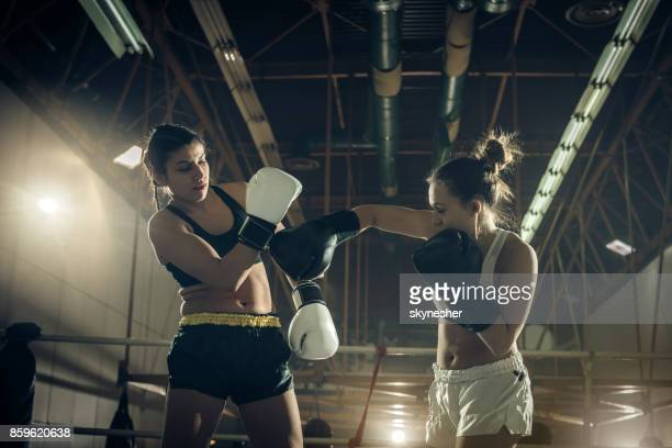 Two young women fighting during a boxing match in a ring.
