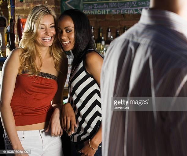 Two young women flirting man in bar