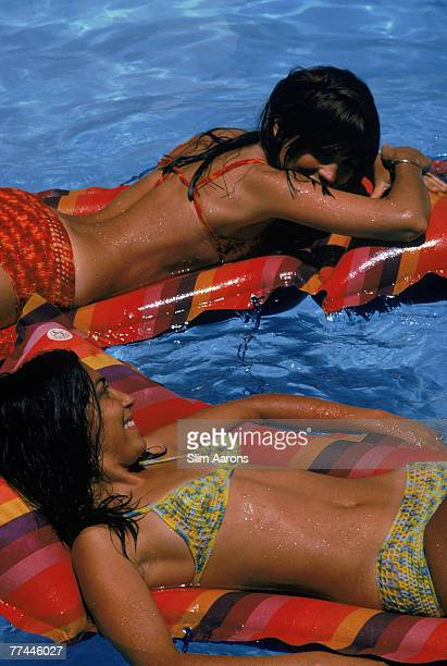 Two young women floating on air beds in a swimming pool at Carvoeiro Portugal July 1970