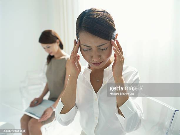 Two young women, focus on woman holding fingers to forehead