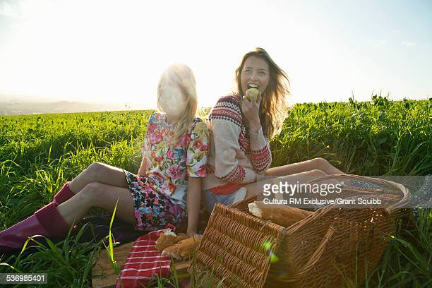 Two young women friends having a picnic in rural field