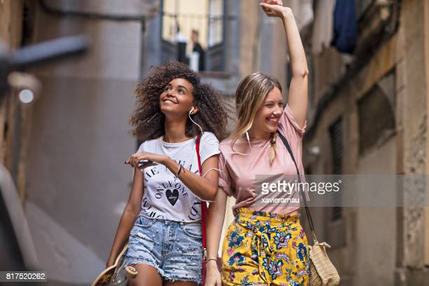 Deux amis de jeunes femmes s'amuser partage de musique dans la rue