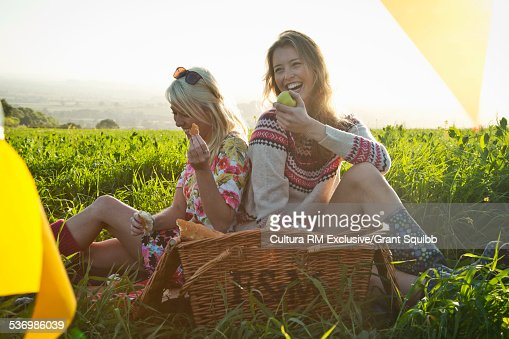 Two young women friends sharing picnic in rural field