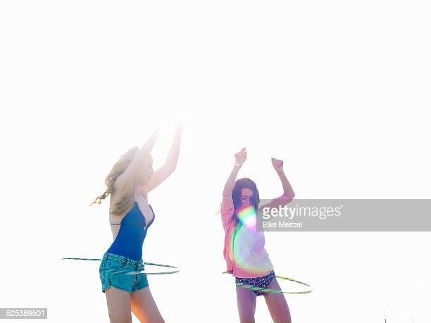 Two young women friends swinging hoola hoops on beach, Williamstown, Melbourne, Australia