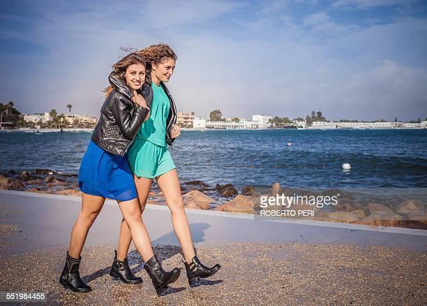 Two young women friends walking on promenade