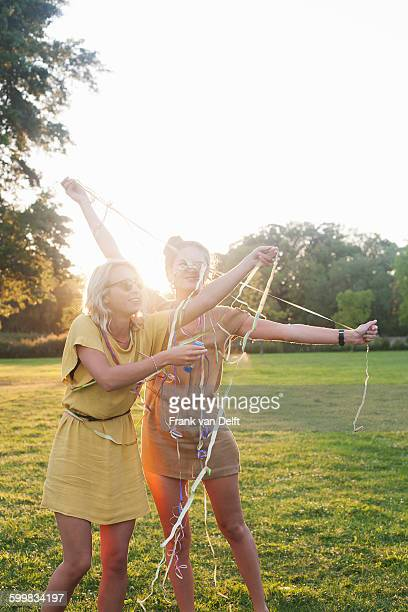 Two young women friends wrapping themselves in streamers at party in park