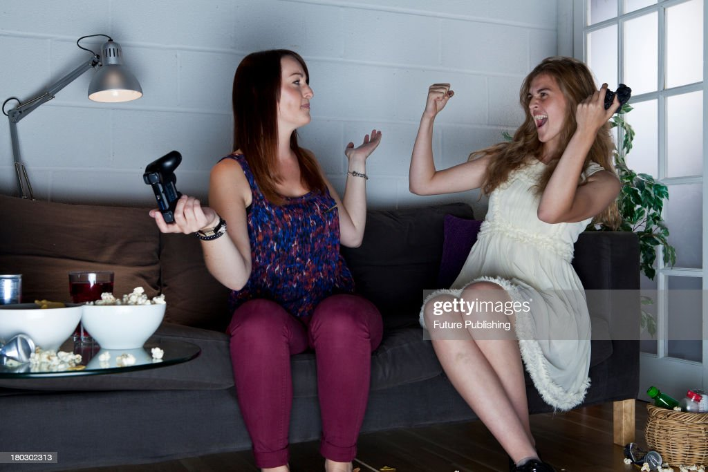 Two young women gesturing, one in victory and the other in defeat, while playing Sony PlayStation 3 video games on a sofa, taken on July 9, 2013.