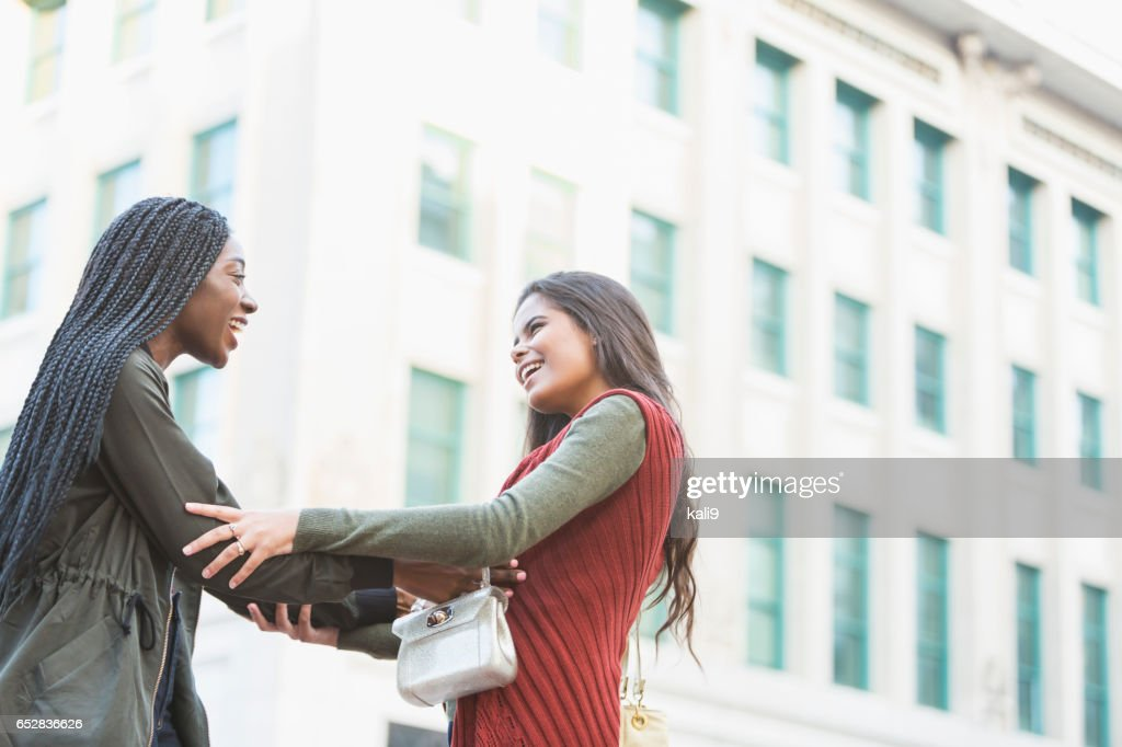 Two young women greeting each other on street corner : Foto stock
