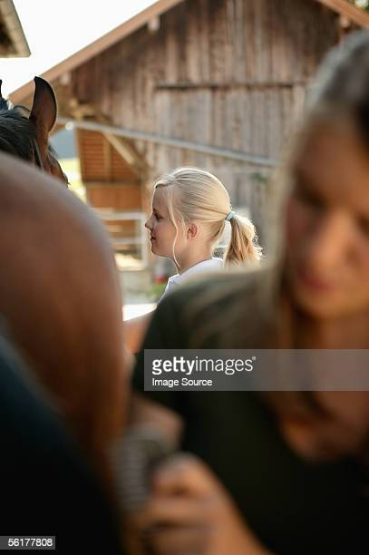 Two young women grooming a horse