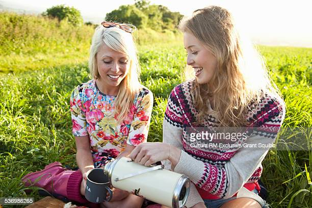 Two young women having a picnic in rural field