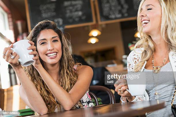 Two young women having coffee in restaurant