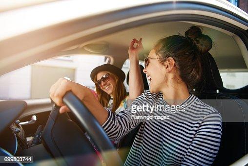 Two young women having fun driving along a street : Stock Photo