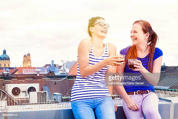 Two young women having fun on balcony, Munich, Bavaria, Germany