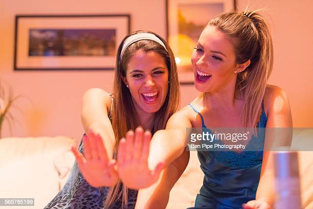 Two young women having girls night in, looking at newly painted nails