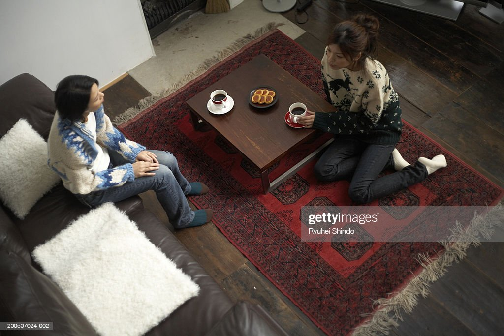 Two young women having tea, elevated view : Stock Photo