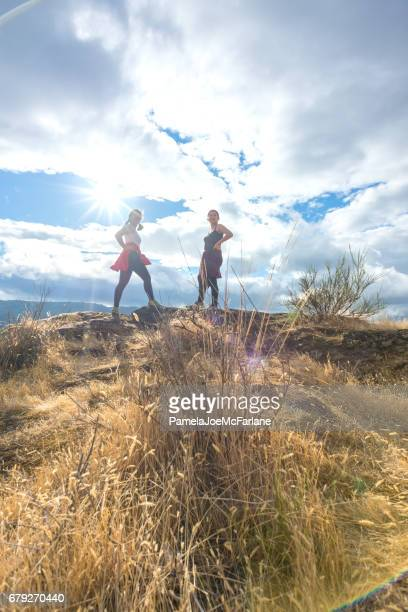 Two Young Women Hikers Look Down from Mountain Top