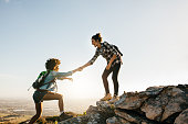 Young woman helping friend to climb up the rock. Two young females hiking in nature.