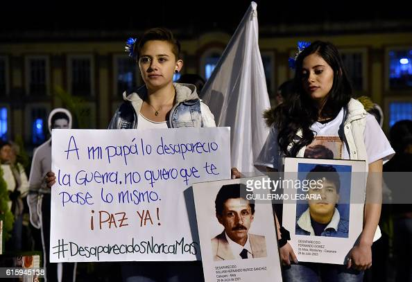 Two young women hold signs during a march for peace in Bogota on October 20 2016 Colombian President Juan Manuel Santos winner of this year's Nobel...