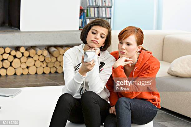 Two young women holding a change purse and looking sad