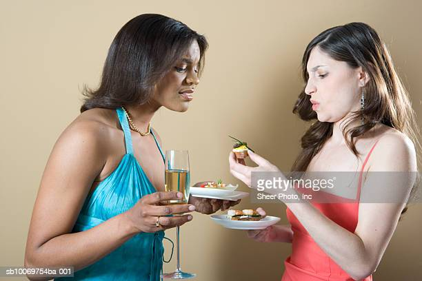Two young women holding appetizers and champagne, studio shot