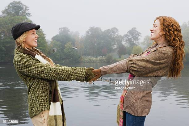 Two young women holding hands in park