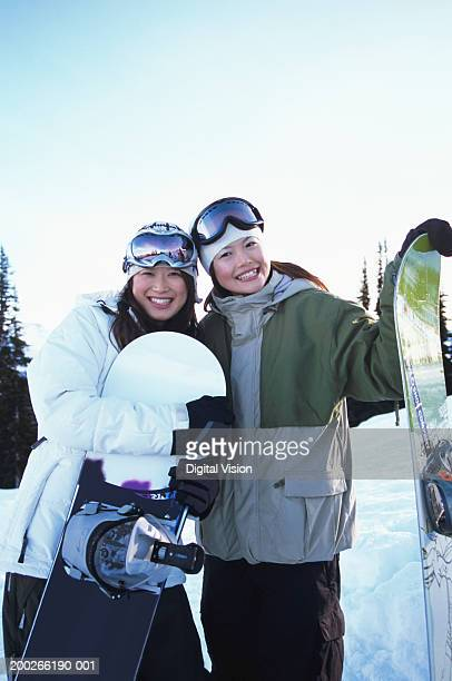 Two young women holding snow boards, smiling, portrait