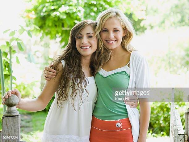 two young women in a garden with their arms around each other