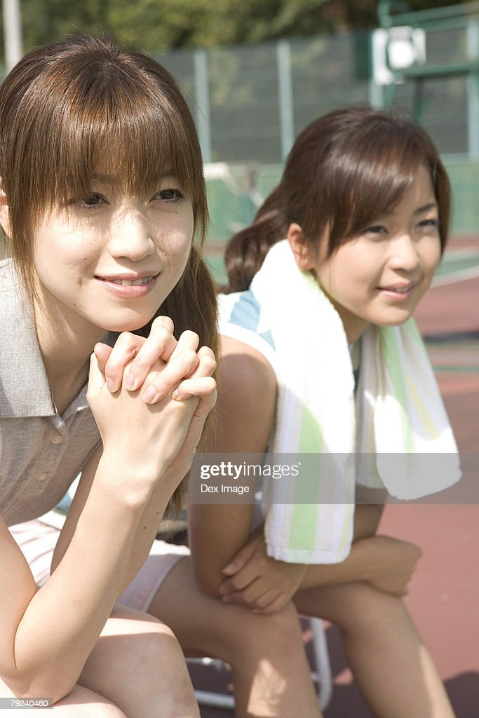 Two young women in a tennis court, resting : Stock Photo