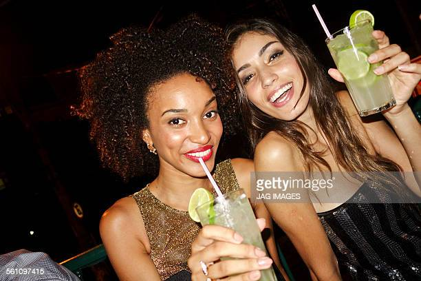Two young women in bar, drinking cocktails, looking at camera, smiling