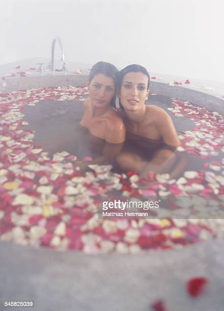 Two Young Women in Bathtub with Petals