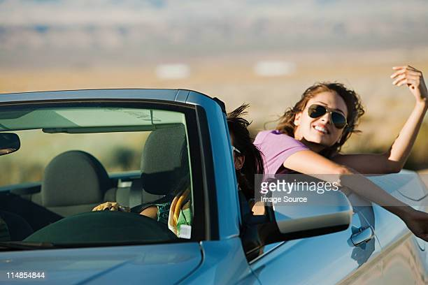Two young women in convertible car