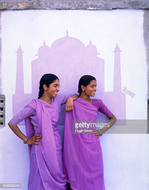 Two young women in front of mural painting of Taj Mahal wearing sari, India
