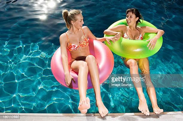 Deux jeunes femmes sur des anneaux gonflables dans la piscine