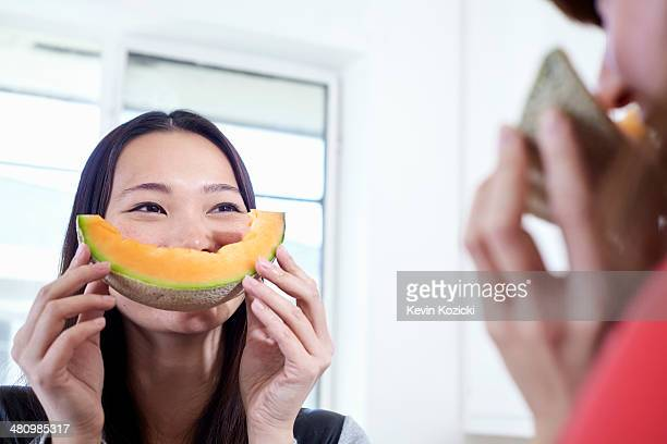 Two young women in kitchen with melon mouths