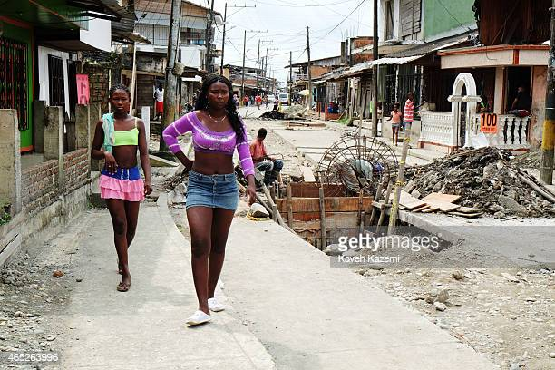 BUENAVENTURA COLOMBIA JANUARY 15 2015 Two young women in mini skirts walk past road works in La Playita neighborhood on January 15 2015 in...