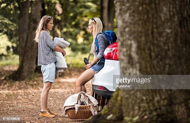Two young women in nature talking to each other.