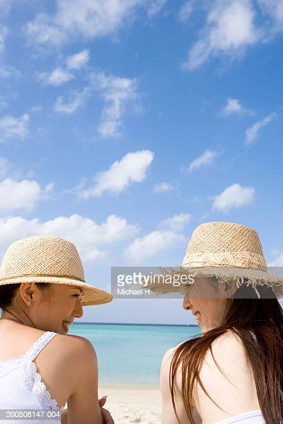 Two young women in sun hats sitting on beach, smiling, rear view