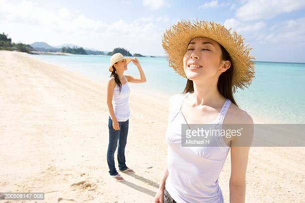 Two young women in sun hats standing on beach, smiling