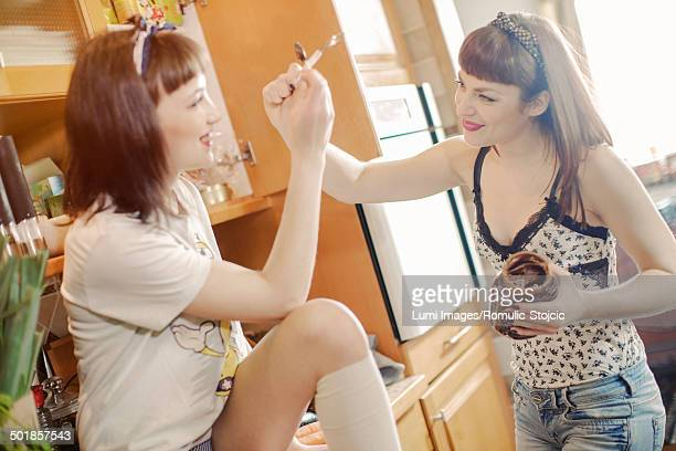 Two young women in the kitchen fooling around