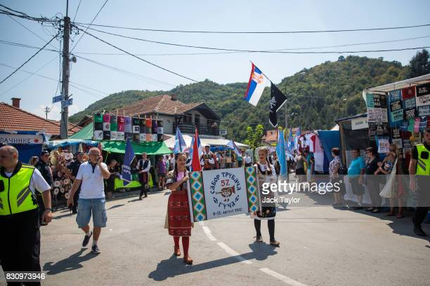 Two young women in traditional Serbian dress parade through the town displaying a sign for this year's Guca Trumpet Festival on August 12 2017 in...