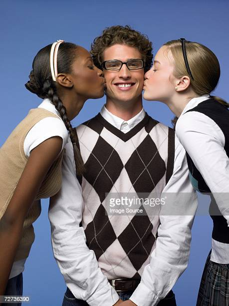 Two young women kissing a man